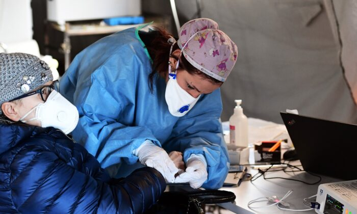 A elderly woman receives assistance in the a pre-triage medical tent in front of the Cremona hospital in Cremona, northern Italy, on March 4, 2020. (Miguel Medina/AFP via Getty Images)