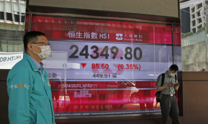 Men wearing face masks stand in front of an electronic board showing Hong Kong share index outside a local bank in Hong Kong, on April 15, 2020.  (Kin Cheung/AP Photo)