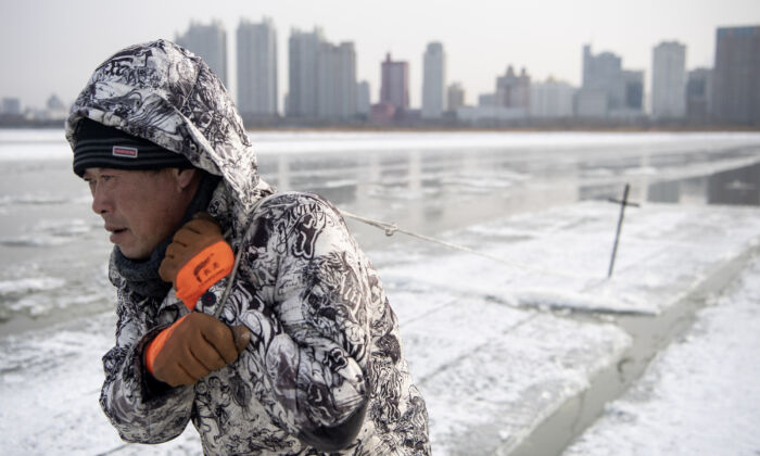 A worker drags ice blocks on the frozen Songhua river in Harbin, China, on Dec. 11, 2019. (Noel Celis/AFP via Getty Images)