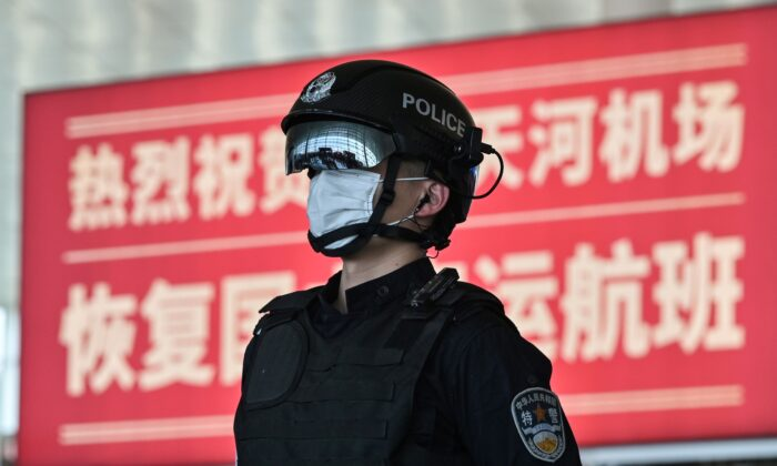A police officer wearing a face mask stands guard at the Tianhe Airport after it was reopened today, in Wuhan in China's central Hubei province on April 8, 2020. (Hector Retamal/AFP via Getty Images)