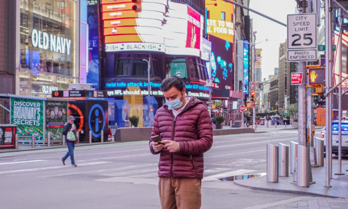 A man wearing a medical face mask is using his phone at Times Square, New York, on April 4, 2020. (Chung I Ho/The Epoch Times)