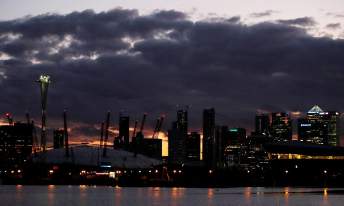Canary Wharf is seen with the O2 arena, illuminated blue in support of NHS and other key workers as the number of coronavirus cases increases globally, London, Britain, April 2, 2020. (Paul Childs/Reuters)