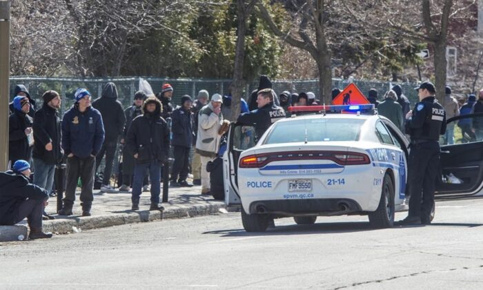 Police remind people to keep their social distance as they lineup to get into a homeless shelter in Montreal on March 31, 2020. (Ryan Remiorz/The Canadian Press)