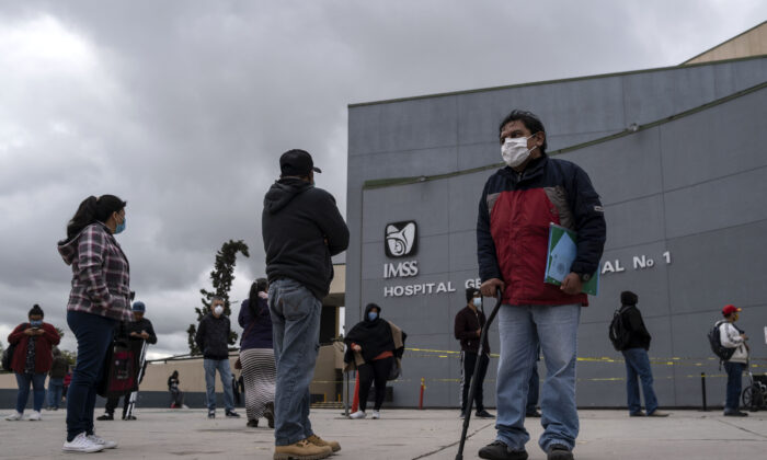 People wearing face masks as a preventive measure against the spread of COVID-19, line up to access the IMSS General Hospital Regional 1 in Tijuana, Baja California State, Mexico, on April 13, 2020 during the novel coronavirus pandemic. (Guillermo Arias/AFP via Getty Images)
