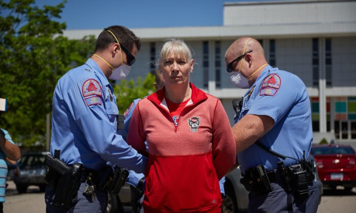 A protester from a grassroots organization called ReopenNC is arrested after refusing to leave a parking lot during a demonstration against the North Carolina CCP virus lockdown at the North Carolina State Legislature in Raleigh, North Carolina, on April 14, 2020. (Logan Cyrus/AFP via Getty Images)