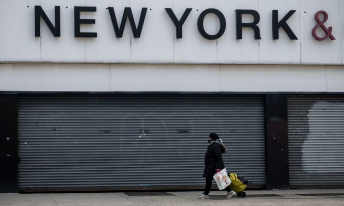 A woman wearing a mask walks past closed store fronts in the Astoria neighborhood of Queens, New York City on April 15, 2020. (Johannes Eisele/AFP via Getty Images)