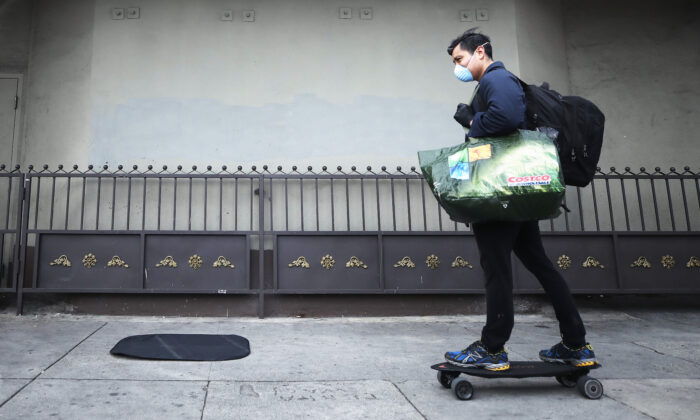 A man skates on the sidewalk while wearing a face mask and carrying bags in Los Angeles, California, on March 20, 2020. (Mario Tama/Getty Images)