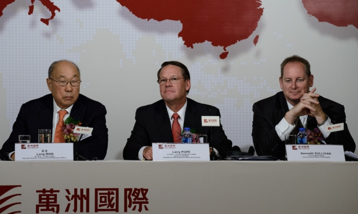 File photo: Executive director and chairman of WH Group, Wan Long, Executive director and president of Smithfield, Larry Pope and Smithfield chief financial officer, Kenneth Sullivan attend a press conference in Hong Kong on April 14, 2014. (Philippe Lopez/AFP via Getty Images)