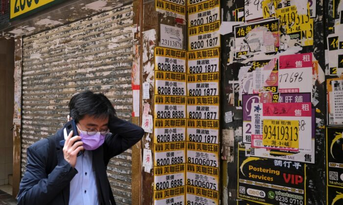A man wearing protective mask walks past a closed shop covered with advertisements for rental space at Mongkok, following the outbreak of the COVID-19, in Hong Kong, China, on March 13, 2020. (Tyrone Siu/Reuters)