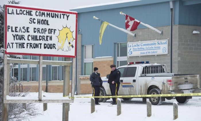 Members of the RCMP stand outside the La Loche Community School in La Loche, Sask. on Jan. 25, 2016. (The Canadian Press/Jonathan Hayward)