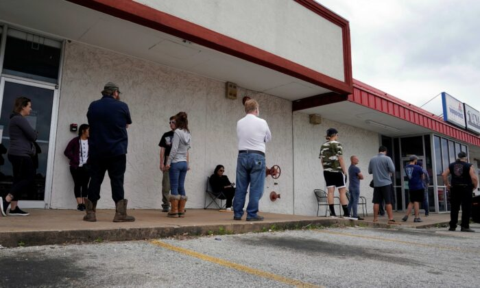 People who lost their jobs wait in line to file for unemployment following an outbreak of COVID-19 at an Arkansas Workforce Center in Fayetteville, Arkansas, on April 6, 2020. (Nick Oxford/Reuters)