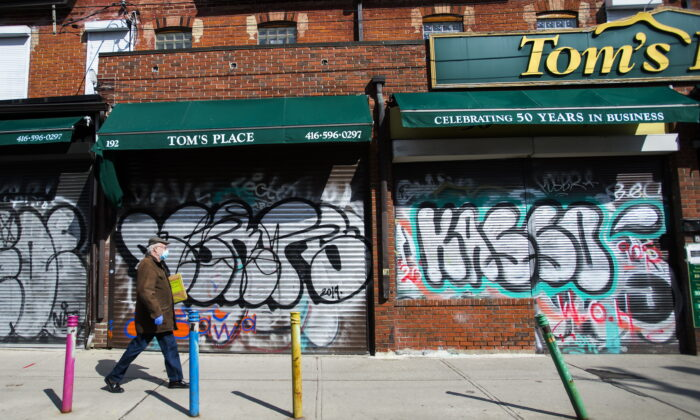 A lone person walks past closed businesses in Kensington Market in Toronto on April 15, 2020. (Nathan Denette/The Canadian Press)