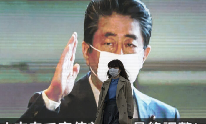 A pedestrian wearing a face mask walks in front of a monitor displaying an image of Japan's Prime Minister Shinzo Abe during a news broadcast  in Tokyo, Japan, on April 06, 2020. (Tomohiro Ohsumi/Getty Images)