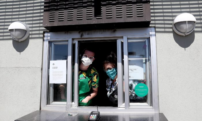 Starbucks employees wear a mask while working the drive-thru window in Edgewater, Colorado, on April 7, 2020. (Matthew Stockman/Getty Images)