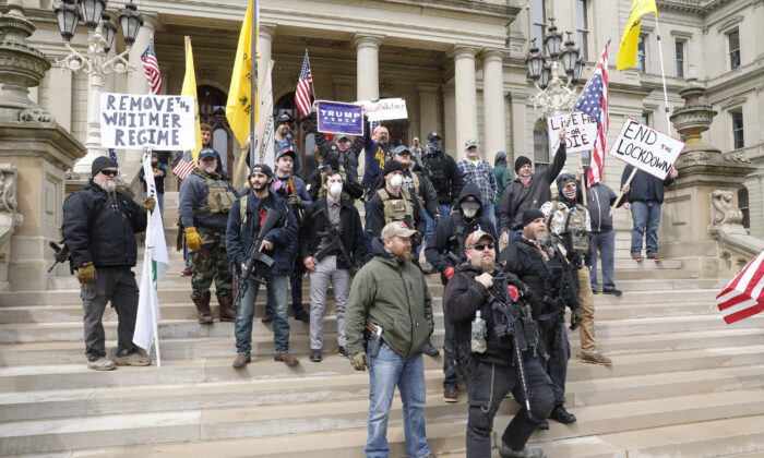 """People take part in a protest for """"Michiganders Against Excessive Quarantine"""" at the Michigan State Capitol in Lansing, Michigan on April 15, 2020. (Jeff Kowalsky/AFP via Getty Images)"""