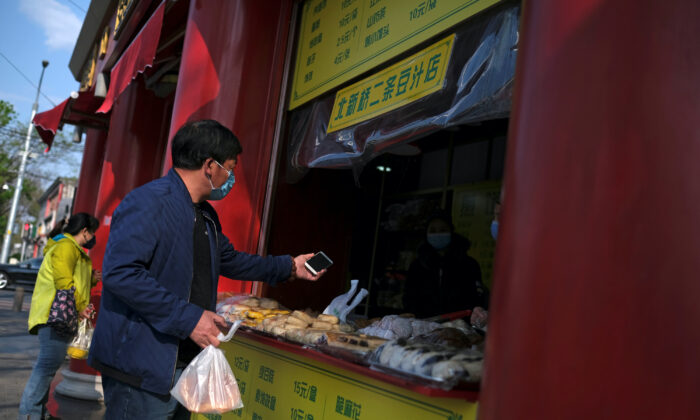 People wearing face masks buy food at a restaurant in Beijing, following an outbreak of the COVID-19 disease in China on April 17, 2020. (Carlos Garcia Rawlins/Reuters)