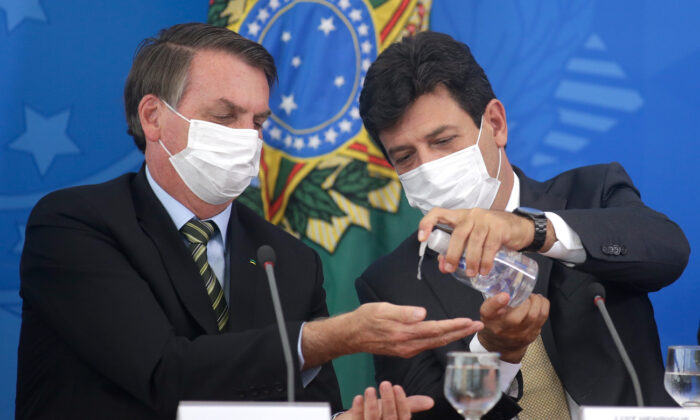 Brazilian Health Minister Luiz Henrique Mandetta gives gel alcohol to President Jair Bolsonaro, both using protective masks, during a press conference about government plans and measures about the CCP virus crisis in Brazil, at the Planalto Palace in Brasilia, Brazil on March 18, 2020. (Andre Coelho/Getty Images)
