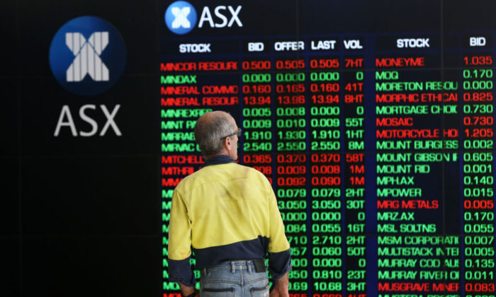 A man looks at an electronic board displaying stock information at the Australian Securities Exchange, operated by ASX Ltd. in Sydney, Australia, March 16, 2020 (by Brendon Thorne/Getty Images)