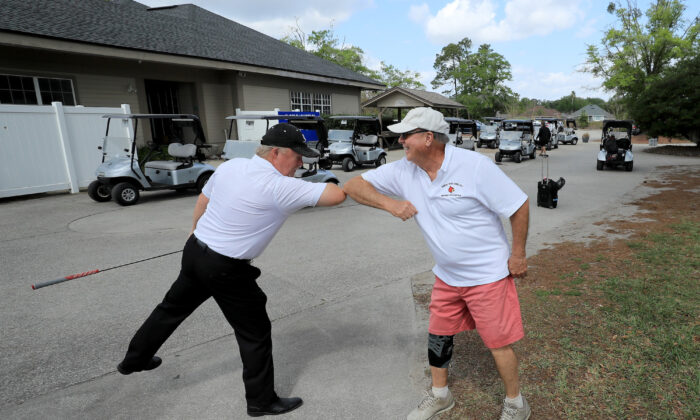 Golfers bump elbows at Windsor Parke Golf Club in Jacksonville Beach, Florida, on March 25, 2020. (Sam Greenwood/Getty Images)