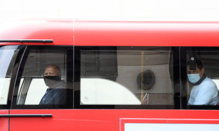 Two passengers wearing masks are seen on a bus in London, UK, on April 17, 2020. (Reuters/Toby Melville)