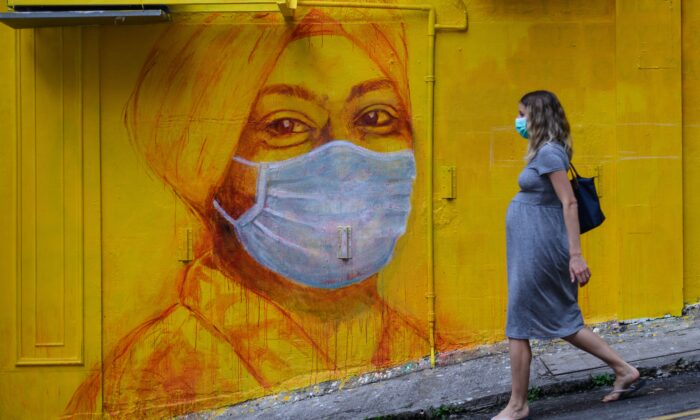 A pregnant woman wearing a face mask as a precautionary measure walks past a street mural in Hong Kong, on March 23, 2020. (Anthony Wallace/ AFP via Getty Images)