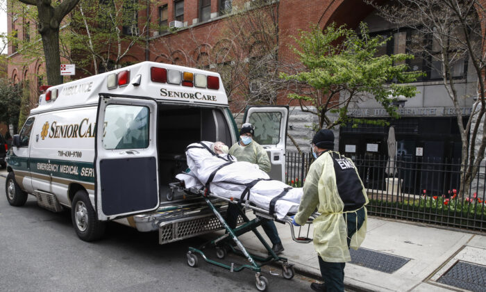 A patient is loaded into the back of an ambulance by emergency medical workers outside Cobble Hill Health Center in the Brooklyn borough of New York City on April 17, 2020. (John Minchillo/AP Photo)