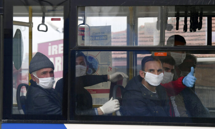 Prisoners sit in a bus in Sincan outside Ankara, Turkey on April 15, 2020. (AP)