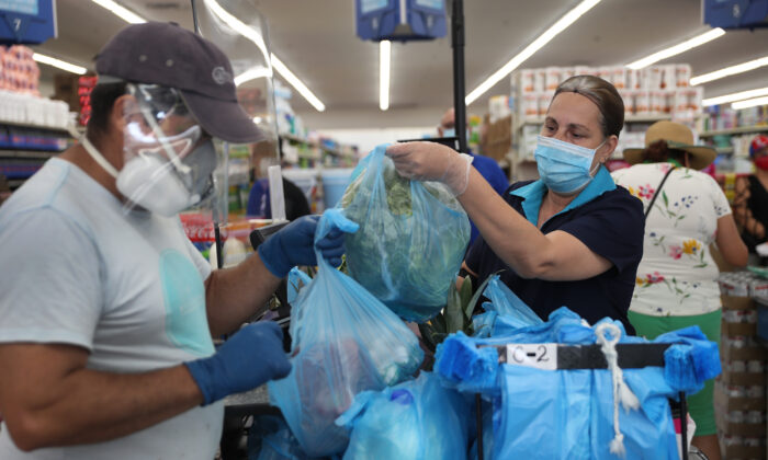 A cashier wears a mask and gloves at the Presidente Supermarket in Miami on April 13, 2020. (Joe Raedle/Getty Images)