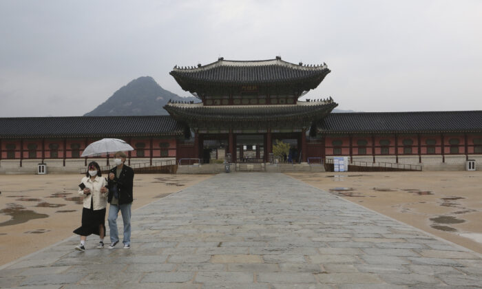 A couple wearing face masks to help protect against the spread of the CCP virus walks in the rain at the Gyeongbok Palace, the main royal palace during the Joseon Dynasty, in Seoul, South Korea, April 17, 2020. (Ahn Young-joon/AP Photo)