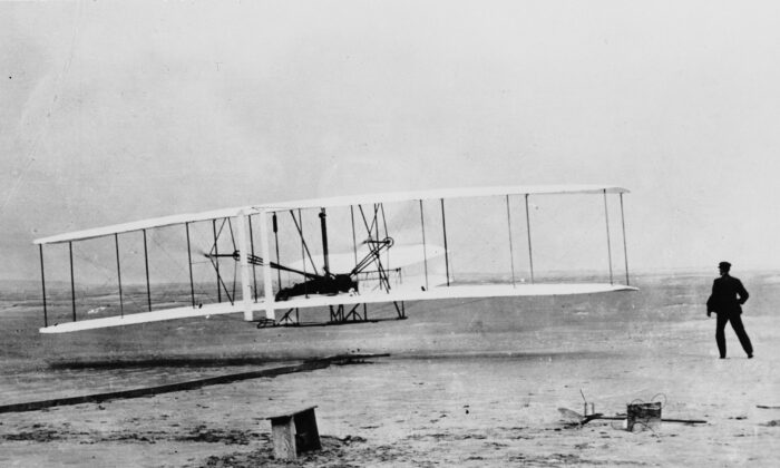 Orville Wright flying a Wright glider at Kill Devil Hills, near Kitty Hawk, North Carolina. The flight was officially the first sustained, controlled flight by a heavier-than-air craft. Wilbur Wright runs alongside his brother. (Fox Photos/Getty Images)