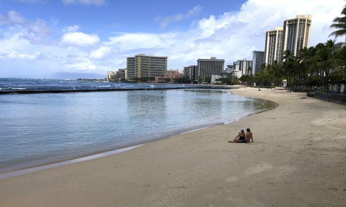 A couple sits on an empty section of Waikiki Beach in Honolulu on March 28, 2020. (Caleb Jones/AP Photo)