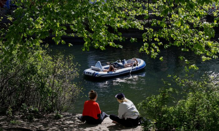 People sit in the sun as others relax in an inflatable boat along the Landwehr canal in Berlin's Kreuzberg district on April 18, 2020. (David Gannon/AFP via Getty Images)