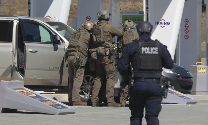 Royal Canadian Mounted Police officers prepare to take a suspect into custody at a gas station in Enfield, Nova Scotia, on April 19, 2020. (Tim Krochak/The Canadian Press via AP)