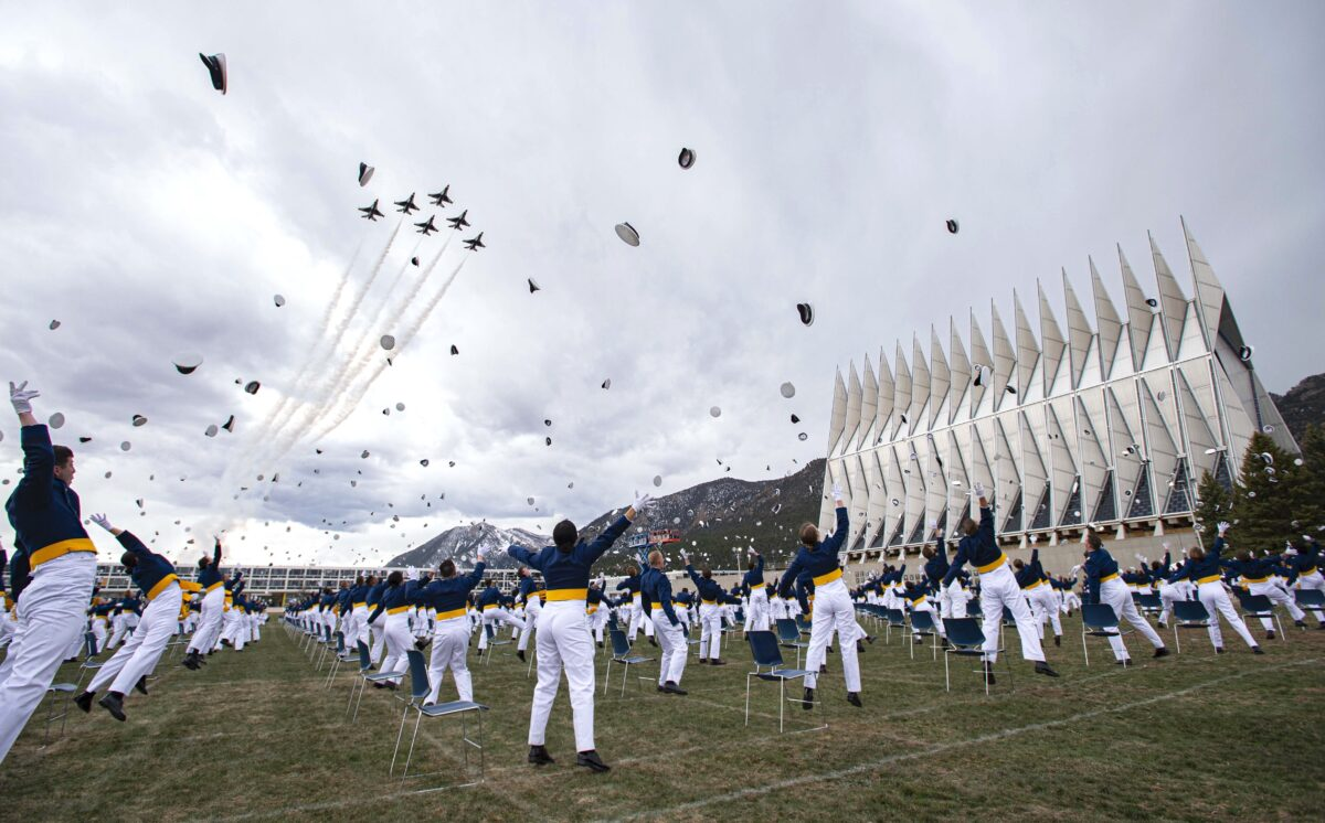The class of 2020 toss their caps into the air