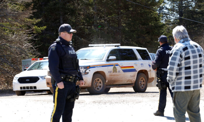 A Royal Canadian Mounted Police (RCMP) SUV pulls up to the end of Portapique Beach Road while an officer speaks with a man after the police finished their search for shooter Gabriel Wortman, in Portapique, Nova Scotia, Canada on April 19, 2020. (John Morris/Reuters)