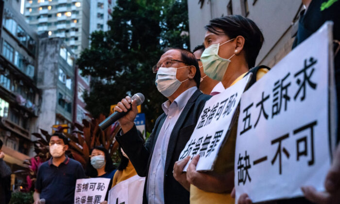 Pro-democracy supporters hold banners and shout slogans outside of the Western District police station in Hong Kong on April 18, 2020,  after at least 14 pro-democracy veterans and supporters were arrested. (Anthony Kwan/Getty Images)