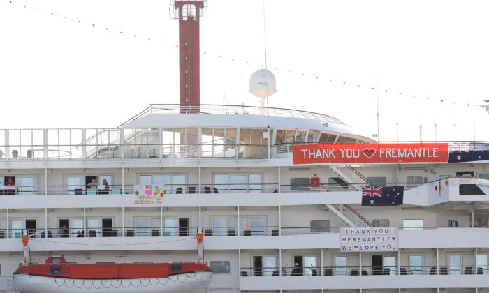 """The MV Artania is seen with """"Thank You Fremantle"""" banners and Australian flags positioned on the side of the vessel while berthed at the Fremantle Passenger Terminal on March 28, 2020  West Australia. (Photo by Paul Kane/Getty Images)"""