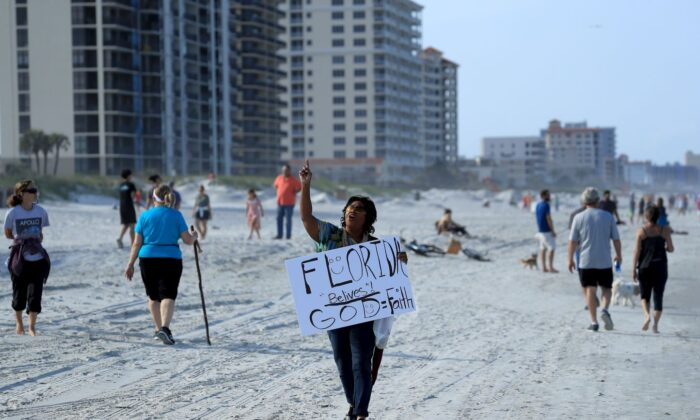 A person carries a sign at the beach in Jacksonville Beach, Florida, on April 17, 2020. (Sam Greenwood/Getty Images)