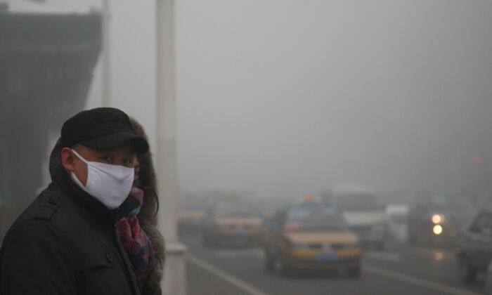 Pedestrians walk along a road as heavy smog engulfs the city in Harbin, China on Dec. 3, 2013. (Getty Images)