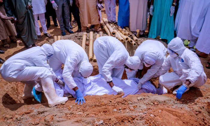 Men wearing protective gear bury the body of Nigerian president's chief of staff, Abba Kyari, who died on Friday after contracting COVID-19, at Gudu Cemetery in Abuja, Nigeria April 18, 2020. (Nigeria Presidency/Handout via Reuters.)