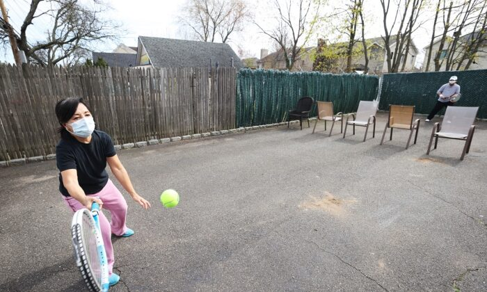 Ana Diaz, a nurse at Northwell Syosset Hospital, plays tennis with her husband Melanio on a makeshift court they created on the driveway of their home in Merrick, New York, on April 19, 2020. (Al Bello/Getty Images)