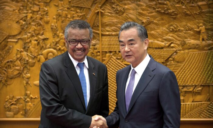 WHO Director-General Tedros Adhanom Ghebreyesus shakes hands with Chinese Foreign Minister Wang Yi as he arrives for a meeting at the Ministry of Foreign Affairs in Beijing, on July 17, 2018. (AP Photo/Mark Schiefelbein, Pool)