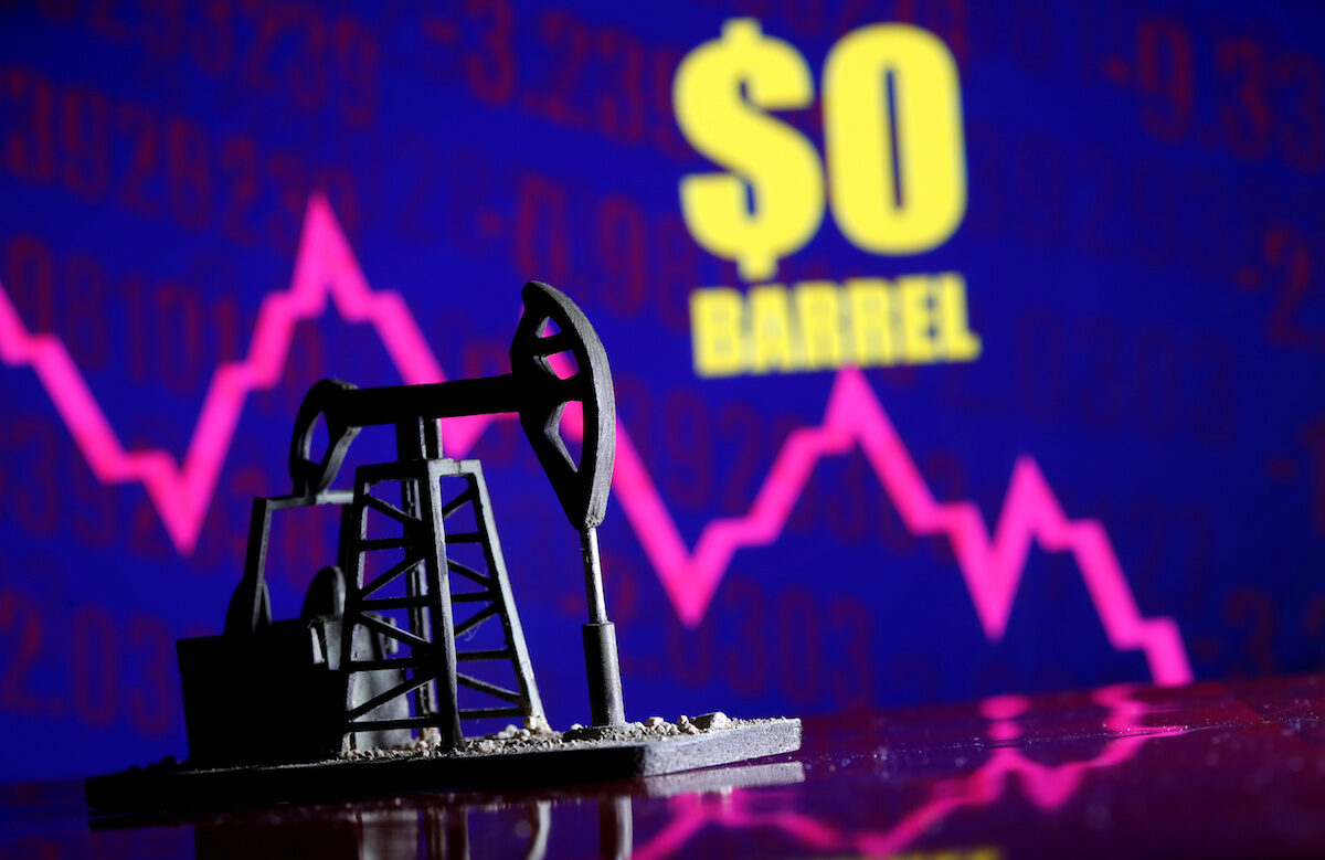 """A 3D-printed oil pump jack is seen in front of displayed stock graph and """"$0 Barrel"""" words in this illustration picture"""