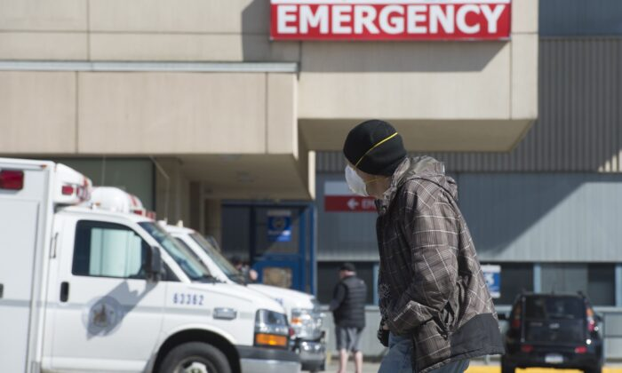 A man wearing a protective face mask walks past the emergency department of the Royal Columbian Hospital in New Westminster, B.C., on April 3, 2020. (The Canadian Press/Jonathan Hayward)
