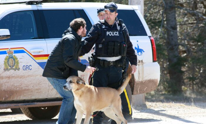 A Royal Canadian Mounted Police (RCMP) officer returns a dog to an individual since the road is shut down after a manhunt for Gabriel Wortman, who they describe as a shooter of multiple victims, in Portapique, Nova Scotia, Canada, on April 19, 2020. (John Morris/Reuters)