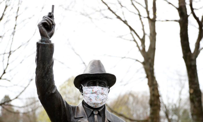 "A protective mask adorns a statue entitled ""the starter"" near the Boston Marathon starting line in Hopkinton, Massachusetts on April 20, 2020. (Maddie Meyer/Getty Images)"