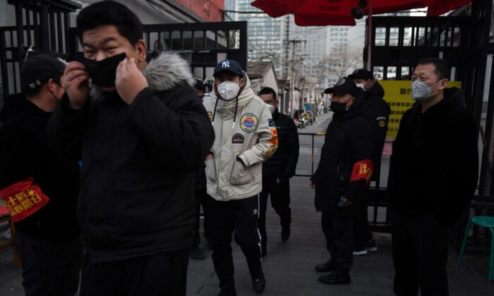 Residents wear face masks as they walk past volunteers manning a checkpoint at the entrance to an alley in Beijing on Feb. 21, 2020. (Greg Baker/AFP via Getty Images)