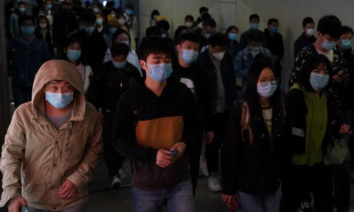 Những người đi làm đeo mặt nạ bảo vệ khi họ thoát khỏi một chuyến tàu tại ga tàu điện ngầm trong giờ cao điểm ở Bắc Kinh, Trung Quốc vào ngày 20 tháng 4 năm 2020. (Lintao Zhang / Getty Images)