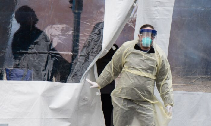 A health professional walks out of a drive-thru coronavirus testing site at the University of Dayton in Dayton, Ohio, on March 17, 2020.   (MEGAN JELINGER/AFP via Getty Images)