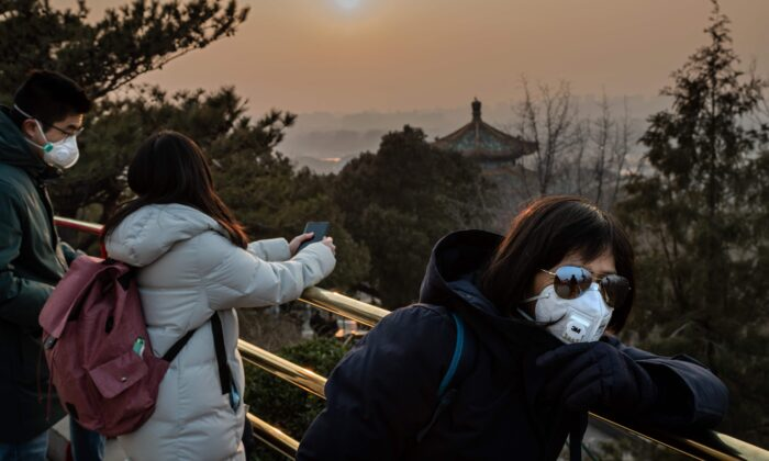 Tourists wearing protective facemasks to help stop the spread of a deadly SARS-like virus which originated in the central city of Wuhan, look at the sunset at Jingshawn park overlooking the Forbidden City in Beijing on Jan. 25, 2020. (NICOLAS ASFOURI/AFP via Getty Images)